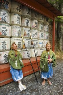 Men traditional clothing sitting in front of colourful sake barrels