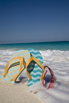 Two mismatched beach flip-flops with red sunglasses in the surf on a Caribbean beach