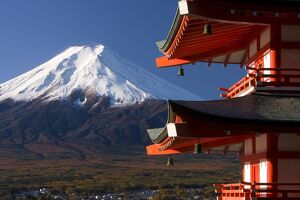 Mount Fuji capped in snow and the upper levels of a temple