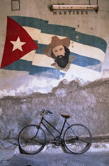 Mural of Camilo Cienfuergos on wall above a bicycle, Havana, Cuba, West Indies