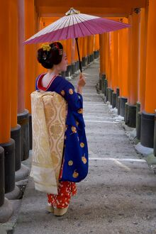 Portrait of a geisha holding an ornate umbrella at
