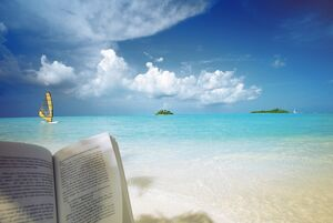 Reading book on the beach, windsurfing and islands in the distance, the Maldives