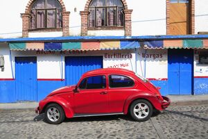 Red Volkswagon Beetle parked on cobblestone street, Tepoztlan, near Mexico City where many city dwellers spend weekends, Morelos, Mexico,