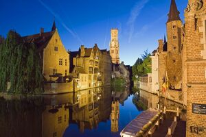 Reflection in canal of Belfort (belfry tower) illuminated at night, Old Town