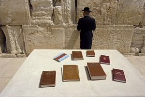 Religious books on table and Jewish man facing the Western Wall