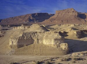 Rock cliffs and sand dunes in front of the fortress of Masada, in the Judean Desert