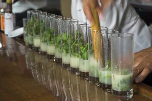 Row of glasses on a bar with barman preparing mojito cocktails, Habana Vieja