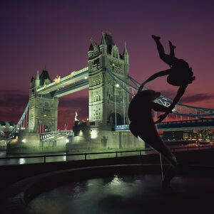 Silhouetted fountain statue and Tower Bridge illuminated at night, London