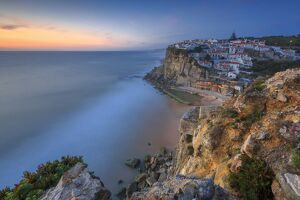The soft colors of twilight frame the ocean and the village of Azenhas do Mar, Sintra