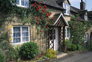 Stone cottages with roses on the walls in the Cotswolds village of Winchcombe