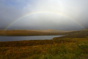 Stormy sky and rainbow over a Loch, Highlands, Scotland, United Kingdom, Europe