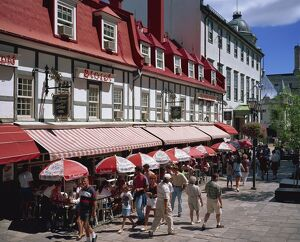 Street scene with hotel, restaurants and pavement cafes on Place d'Armes in Quebec City