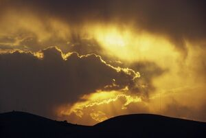 Sun behind dark clouds at sunset over hills at Guanajuato