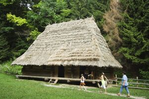 Tourists visiting traditional thatched roof house in