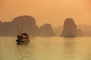 Traditional boat sailing through limestone archipelago at sunset, Ha Long Bay, UNESCO World Heritage Site, Northeast, Vietnam, Indochina, Southeast Asia, Asia