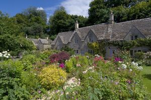 Traditional Cotswold stone cottages with colourful flower gardens, Bibury