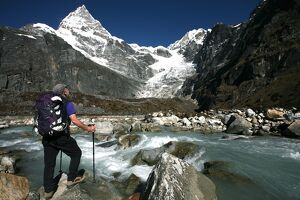 A trekker pauses for a break on the edge of a glacial stream on the way to Mera Peak