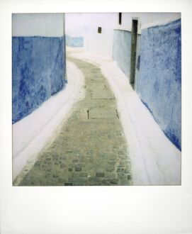 View taken on Polaroid down narrow street showing traditional