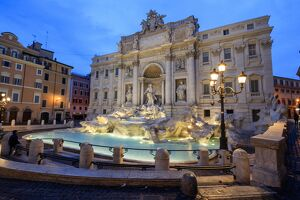 View of Trevi Fountain illuminated by street lamps and the lights of dusk, Rome, Lazio