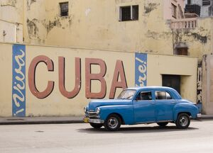 A vintage 1950's American car passing a 'Viva Cuba' sign painted on a wall in cental Havana, Cuba, West Indies,