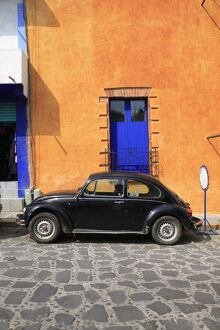 Volkswagon Beetle parked on cobblestone street, Tepoztlan, near Mexico City where many city dwellers spend weekends, Morelos, Mexico,