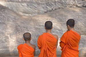 Three young monks praying at a rock-cut image of the