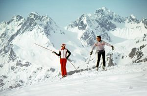 Two Skiers admire the view from a mountain top
