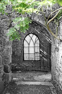 Arched church window in a stone archway in a chapel with green leaves