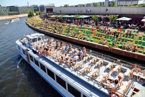 Artificial beach with deckchairs beside the River Spree with a tourist sightseeing boat in Berlin