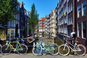 Bicycles on a bridge on the Oudezijds Achterburgwal canal and houses in Amsterdam
