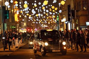 Black taxi cab and Oxford Street Christmas lights in London
