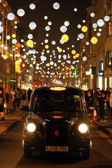 Black taxi cab with Oxford Street Christmas lights in London