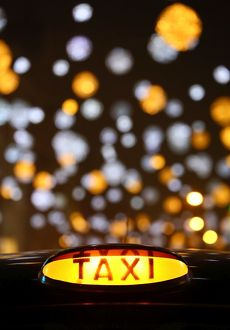 Black taxi cab sign Oxford Street Christmas lights in London