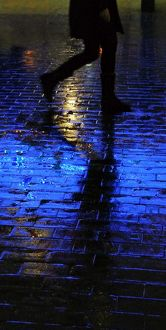 Blue light shining on a wet brick paved pavement surface with shadow of a person