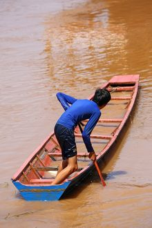 Boy paddling a flooded sinking boat on the Mekong River in Luang Prabang, Laos