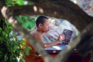 Buddhist monk reading a book at Vat Sop Sickharam temple, Luang Prabang, Laos