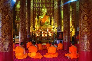 Buddhist monks at worship in Wat Sen temple in Luang Prabang, Laos
