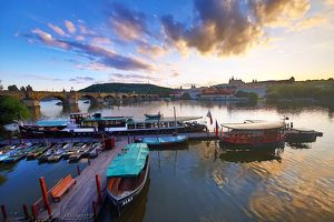 Charles Bridge over the Vltava River and boats at sunset in Prague, Czech Republic