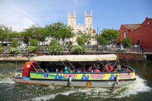 Church of St. Francis Xavier and a tourist sightseeing boat on the Sungai Melaka river in Malacca