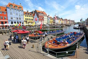 Coloured houses and tourist sightseeing tour boats at Nyhavn Quay in Copenhagen, Denmark