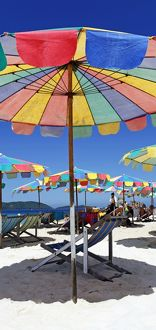 Colourful beach umbrellas and deckchairs for a summer holiday on a tropical sandy beach