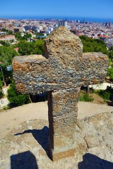 General view of the city skyline and a cross from Parc Guell park in Barcelona, Spain