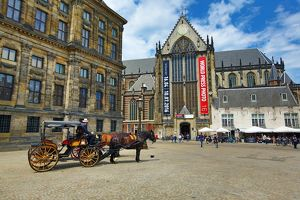Horse drawn carriage and the Nieuwe Kerk church in Dam Square in Amsterdam, Holland