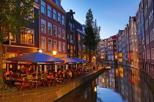 Houses and restaurants on the Oudezijds Achterburgwal canal at sunset in Amsterdam