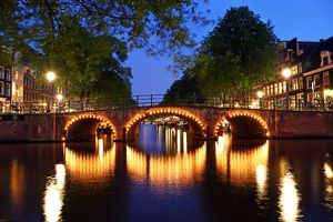 Illuminated canal bridge at night on the canal between Prinsengracht and Brouwersgracht