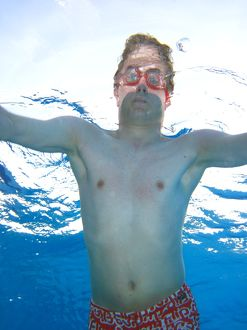 Man swimming underwater wearing goggles