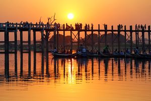 People crossing the U Bein Bridge across the Taungthaman Lake at sunset in Amarapura