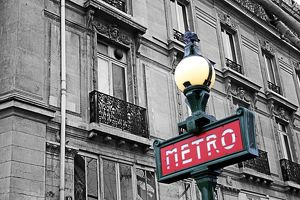Red French Metro subway sign in the street in Paris, France, spot colour