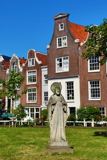 Statue of Jesus Christ and traditional Dutch houses in Begijnhof in Amsterdam, Holland
