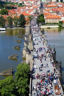 Tourists walking over the Charles Bridge over the Vltava River in Prague, Czech Republic